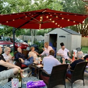 Guests enjoying food and wine outside of Ellen's Wine Room under sun awning