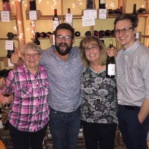 Ellen and friends smiling in front of wine racks
