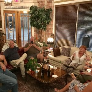 guests lounging and laughing on couches inside of Ellen's Wine Room