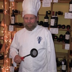 Chef in full Chef attire with spatula at Ellen's Wine Room
