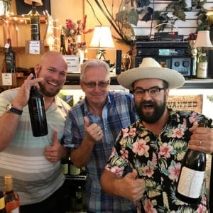 man in floral Hawaiian shirt with friends showing off wine bottles at Ellen's Wine Room