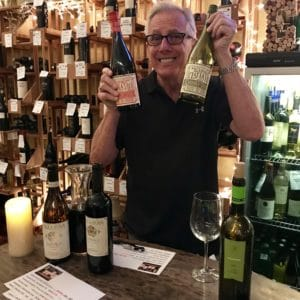 man showing off bottles of wine inside Ellen's Wine Room